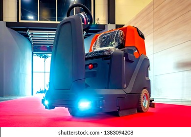 Room cleaning. Clearing service. Walk Behind Scrubber Machine For Cleaning Warehouse Floor. Floor care and cleaning services with washing machine. floor cleaning machine