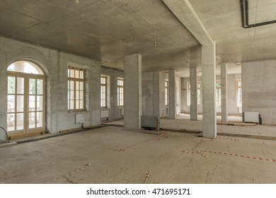 Room with concrete walls and balcony in building under construction without finishing