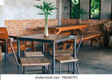 A room with dark tone wood and steel table and chairs, wooden bench with glass vase and green plant on industrial loft style red brick and concrete wall and floor background. Selective focus.