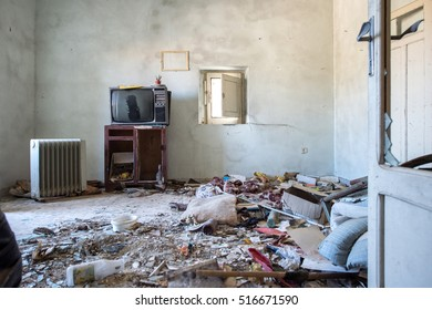 Room destroyed with furniture, old television and garbage in Alianello, Italy
