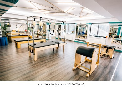 Room full of pilates equipment: exochairs, ladder barrel, reformer, cadillac and trapeze table