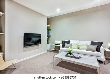 Room has a tv on the wall near a wooden chair, floor has a wool carpet. a small white table made in  ceramic and steel middle of the room, there is a vase fills with white flowers and two mugs