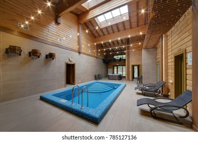 The room with high ceilings and wooden beams with the pool