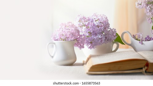 Room interior with blooming lilacs flower bunch in jug, old vintage open fairytale book on table, tender romantic spring home decor in soft morning light, reading literature concept, empty copy space