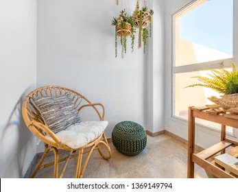 Room interior with rattan chair with cushion, macrame hanging plants and fiber pouf in a living room with a big window. Relax lecture retreat room. Hygge decoration concept.