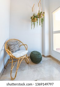 Room interior with rattan chair with cushion, macrame hanging plants and fiber pouf in a living room with a big window. Lecture retreat room. Boho style relaxation decoration concept.