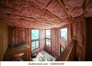 Room interior walls with pink color thermal insulation installed prior to drywall installation