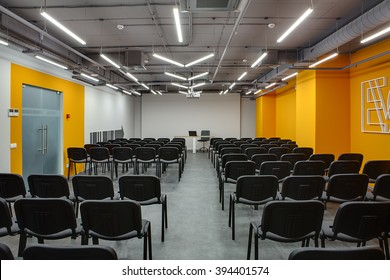 Room for lecture with a lot of chairs. Chairs are gray with black. Left and back walls are white, right wall is orange. On the left wall there are translucent doors with orange colored frame. There is