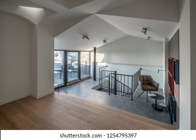 Room in a modern style with white walls and design false ceiling, parquet and dark tiles on the floor. There is a window with glass door to terrace, black staircase, armchair, shelves, table, lamps.