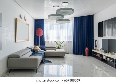 Room in a modern style with white walls and light tiled floor. There is a stand with a white tabletop with decorations and dark shelves, TV, red vase, gray sofas, fancy red lamp, plants in the pots.