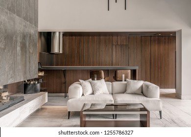 Room in a modern style with white and wooden walls and a tiled floor. There is a fireplace, black bag with firewood, sofa with pillows, glass table, door, tabletop with chairs, chrome kitchen hood.