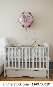 Room of the newborn girl. Crib, gray bed, balloon.