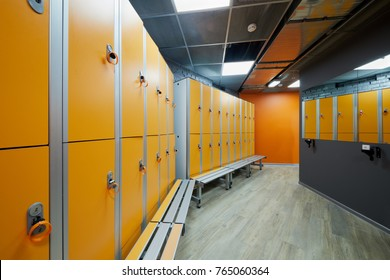 Room with orange lockers at fitness center.