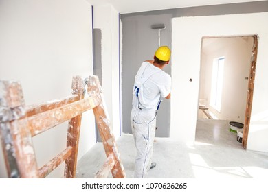Room painter paints a wall in a new home. Unrecognizable Person.
