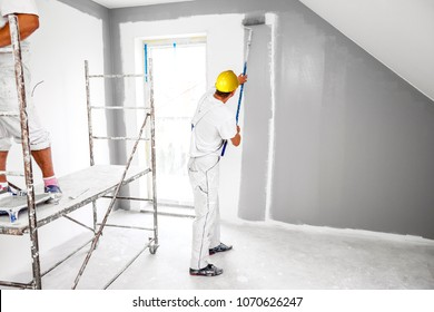 Room painters paints a wall in a new home. Unrecognizable Person.