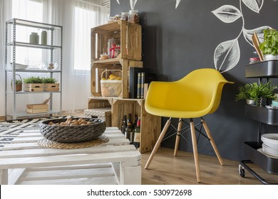 Room with pallets furniture, blackboard and yellow chair