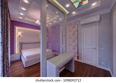 The room with a partition and a bed, a dressing table and a stained-glass window on a ceiling