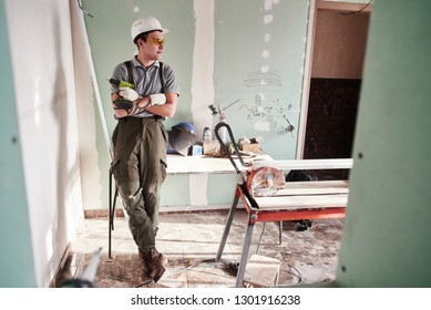 Room repair. Young builder in a helmet and overalls standing with folded hands on the background of the construction site