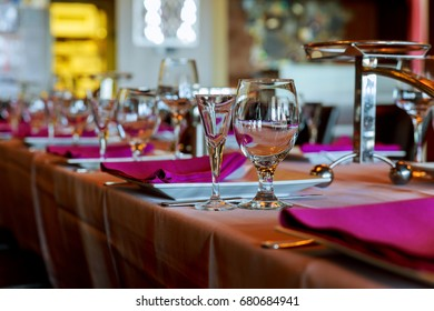 Room with served tables in restaurant, focus on glass in center