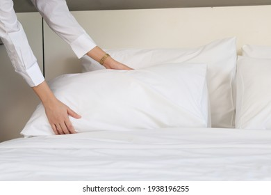 Room service maid cleaning and making bed hotel room concept, female hands of chambermaid holding  pillow for making bed in hotel room.