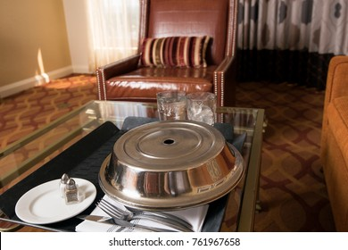 Room service tray in hotel room with stainless steel plate cover, ice tea, water, silverwear, salt and pepper