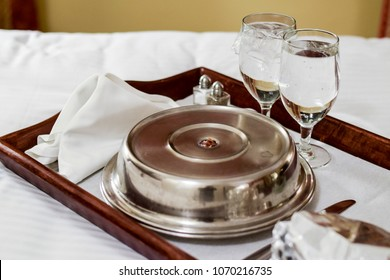 Room service tray on bed in hotel room for dinner