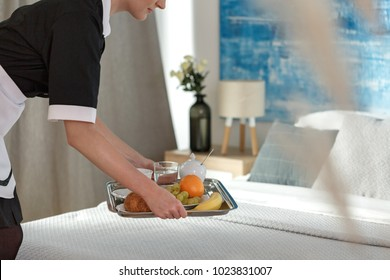 Room service woman bringing breakfast on a tray to a guest's hotel bed