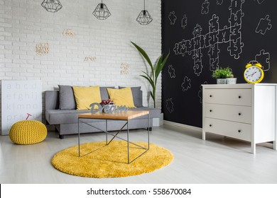 Room with sofa, dresser, blackboard wall and yellow details