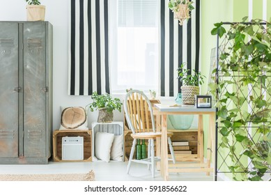 Room with striped window curtain, metal wardrobe, desk and chair