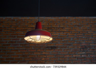 room with vintage red ceiling lamp and brick wall