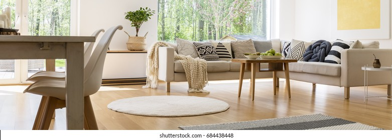 Room with white corner sofa with decorative cushions and blanket