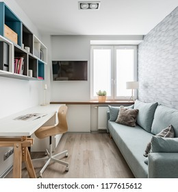 Room with white desk, couch, wall bookcase and patterned wallpaper