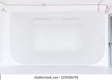 The room with white painted and white floor used for a photo studio, right hand side has a window, is a room suitable for professional photographers and amateurs. Cyclorama wall.