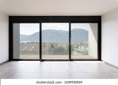 Room with white walls and black window overlooking Lake Maggiore. No one inside
