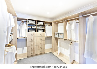 Room with wooden shelves and white dresses hanging under the rack, there are garment baskets with drawers, the floor is a carpet which surrounded by white walls and ceiling