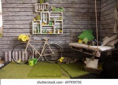 Room with wooden walls with an old bicycle. Sidney with pillows, hanged on ropes.