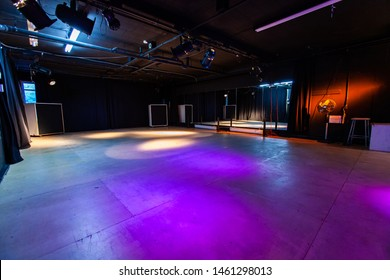 Rooms for rent in community arts center. A wide angle view of an empty dance studio with artificial stage lighting, violet lights shine down on a large dancefloor ready for students to arrive.