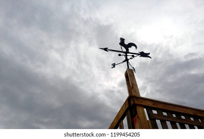 A rooster shaped weathervane and a cloudy sky at the background