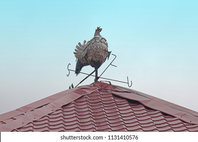 Rooster weather vane figurine on top of the roof with blue sky in the background