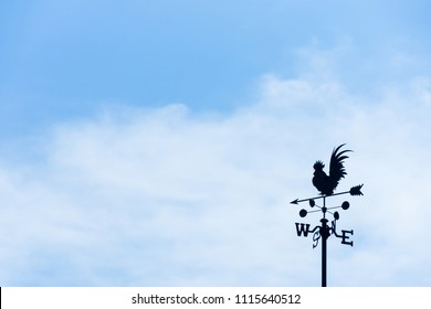 Rooster weather vane on blue sky