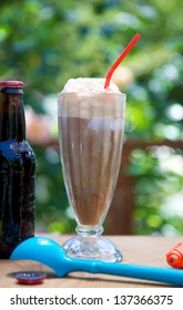 Root beer float outdoors with ice cream scoop and bottle