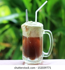 Root beer float, a tasty summer treat.on Green tree background