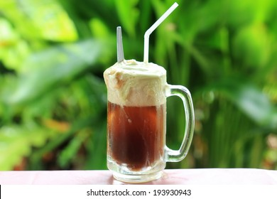 Root beer float a tasty summer treat on Green tree background