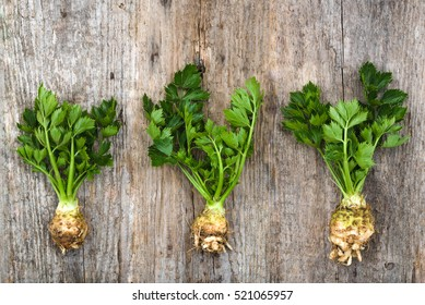 Root of celery with leaves, green vegetables, local market produce on rustic wooden farm table, overhead