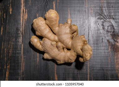 root of ginger lies on black wooden table. background with spice