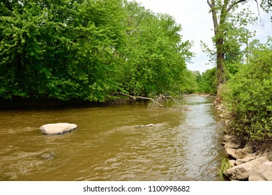 Root River in Racine Wisconsin's Lincoln Park.  The muddy color river flows towards you.
