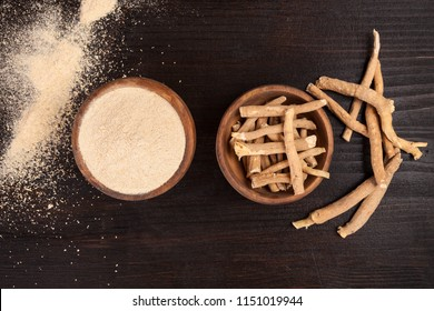 Roots and powder of Ashwagandha also known as Indian ginseng on wooden background, top view.