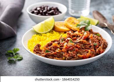 Ropa vieja, un plato tradicional de steak flanco con arroz, habas cubanas y plátanos