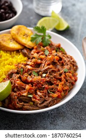 Ropa vieja, traditional flank steak dish with rice, cuban beans and plantains