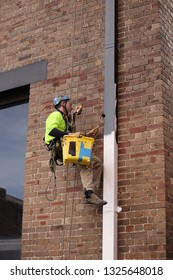 Rope access abseiler handy man building painter commercial services wearing full  safety body harness abseiling setting on the chair while painting down pipe at hight rise building site Sydney CBD,